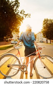 portrait of a beautiful young girl in a hat with a bicycle on city background in the sunlight