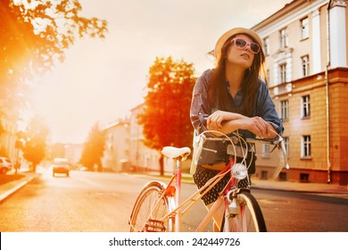 portrait of a beautiful young girl in a hat with a bicycle on city background in the sunlight outdoor