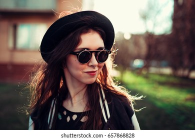 Portrait of a beautiful young girl in hat and glasses with a nose piercing walks through the city at sunset