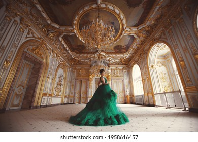 Portrait of a beautiful young girl in a haute couture green dress standing in a luxurious palace interior.