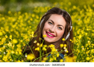 portrait of a beautiful young girl with headphones and yellow flowers in a garden
