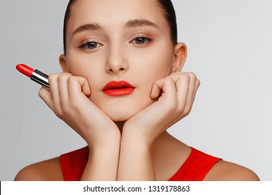 Portrait of a beautiful young girl holding red lipstick in her hand. Gray background