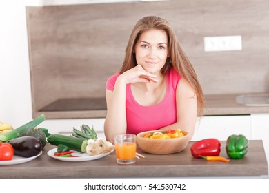 Portrait of a beautiful young girl in the kitchen. Woman preparing a healthy meal of fruits and vegetables. (Shallow DOF; color toned image).
