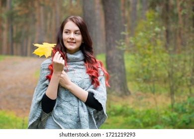 Portrait of a beautiful young girl with long hair and a gray knitted Poncho with a yellow maple leaf in her hand in the autumn forest.