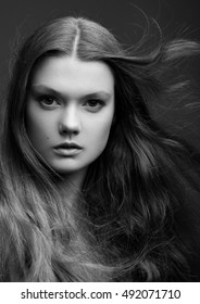 Portrait of beautiful young girl with long hair on grey background black and white