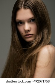 Portrait of beautiful young girl with long hair on grey background