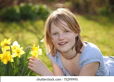 Portrait of a beautiful young girl lying on grass next to some flowers