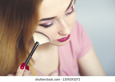 portrait of a beautiful young girl making makeup looking in a pocket mirror in a studio, woman dusting her face with a brush, cosmetics and beauty concept