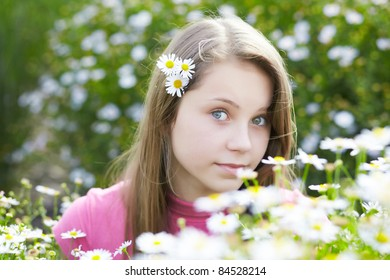 portrait of beautiful young girl in a meadow with camomiles