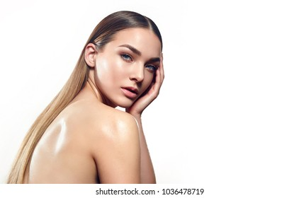 Portrait of a beautiful young girl with natural make-up and well-groomed hair on a white background in the studio.