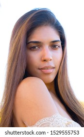 Portrait of a beautiful young girl with a nose ring and long straight hair, looking into the camera