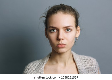 portrait of a beautiful young girl on a gray background, girl with earrings in the ear