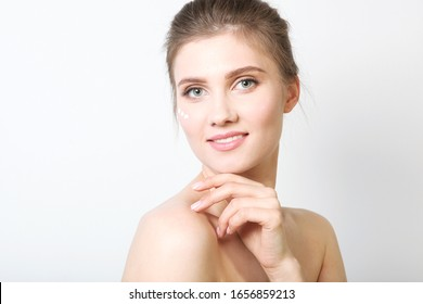 Portrait of a beautiful young girl on a colored background who uses caring cream. The concept of healthy clean skin, spa, skin care.