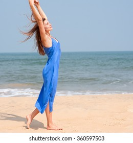 Portrait of a beautiful young girl on the beach in a blue dress in a good mood
