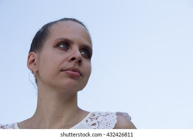 Portrait of a beautiful young girl on a background of the sky