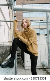 portrait of a beautiful young girl on the roof of the skyscraper on a background of white walls, fashion, model test