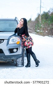 portrait of a beautiful young girl on a background of a winter pine forests and off-road vehicle on a country road