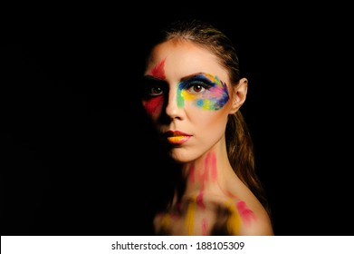 Portrait of a beautiful young girl. Rainbow makeup. Black background