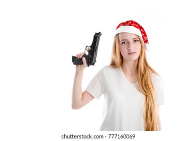Portrait of beautiful young girl in red Santa cap looking at camera and holding a black gun isolated on white background. Happy New Year and Merry Christmas mood winter gangster with free copy space