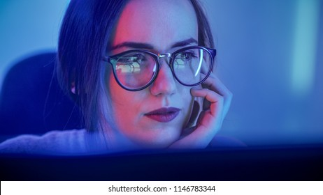 Portrait of the Beautiful Young Girl Sitting Before Computer, Browsing in Internet, Playing Online Games, Streaming. Cute Girls Wearing Glasses in the Cool Retro Neon Lit Room.