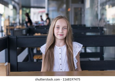 Portrait of beautiful young girl sitting in cafe. Good-looking model with healthy blonde hairstyle. People rest and lifestyle concept. Blurred background