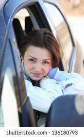 Portrait of beautiful young girl sitting in car and looking to camera