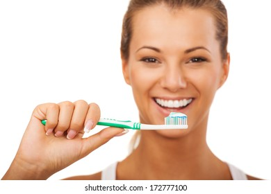 Portrait of beautiful young girl starting to brush her teeth.