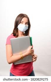 Portrait eines schönen jungen Mädchenschülers einzeln auf weißem Hintergrund mit einem covid-19 Schutz gegen chirurgische Maske