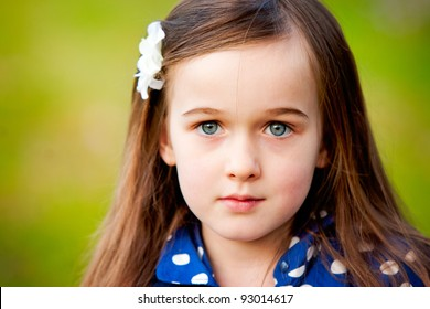 A portrait of a beautiful young girl taken outdoors.  She has a serious express and is making eye contact with the camera.