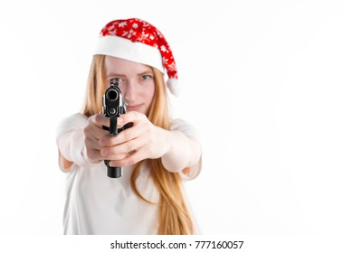 Portrait of beautiful young girl thief in red Santa cap holding a black gun and shooting aimed in camera isolated on white background. New Year and Christmas mood funny gangster or burglar free space