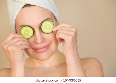 portrait of a beautiful young girl with a towel on her head with cucumber slices in her hands