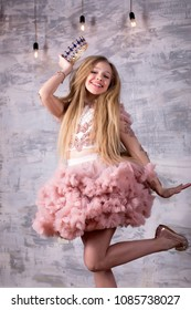 Portrait of a beautiful young girl wearing a fancy pink party gown dress junpink in studio