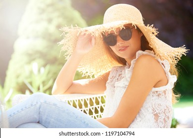 Portrait of beautiful young girl wearing straw hat and sunglasses while relaxing outdoor.
