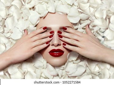 Portrait of a beautiful young girl in white rose petals. Red lips, red fingernails. The girl closes her eyes with her hands.Fashion, beauty, make-up, cosmetics, beauty salon, style, personal care.