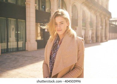 Portrait of a beautiful young girl who is posing in the rays of the setting sun.young attractive blonde girl arrived in a European city to spend a weekend. Sunny day