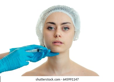 Portrait of a beautiful young girl who looks directly into medical and physician hair Hat gloves touches her face
