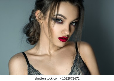 portrait of beautiful young gitl with make up in grey bra looking at the camera
