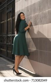 Portrait of beautiful young happy brunette woman in green dress, street summer outdoors