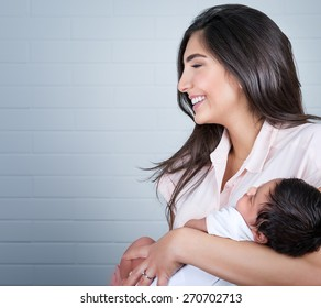 Portrait of beautiful young happy mother having fun with her little newborn baby at home, enjoying first day of motherhood, love and happiness concept