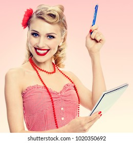 Portrait of beautiful young happy smiling woman with notepad, in pin-up style clothing, over pink background. Caucasian blond model posing in retro fashion and vintage concept studio shoot.
