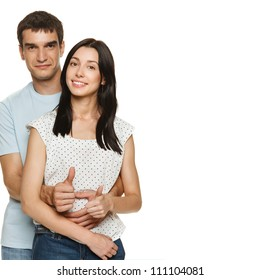 Portrait of a beautiful young happy smiling couple showing thumb up signs, over white background
