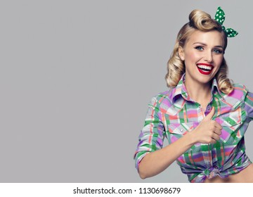 Portrait of beautiful young happy smiling woman, showing thumb up gesture, dressed in pin-up style. Caucasian blond model posing in retro fashion and vintage concept studio shoot, on grey background.