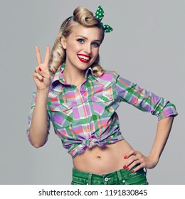 Portrait of beautiful young happy smiling woman, showing two fingers or victory gesture, dressed in pinup style. Caucasian blond model posing in retro fashion and vintage concept studio shot, on grey.