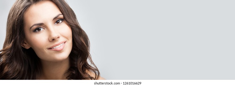Portrait of beautiful young happy smiling woman with long curly hair, with empty copyspace area for slogan, advertising or text message, over grey background.
