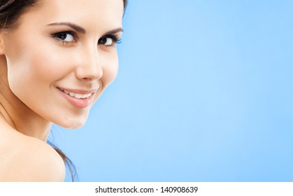 Portrait of beautiful young happy smiling woman, over blue background