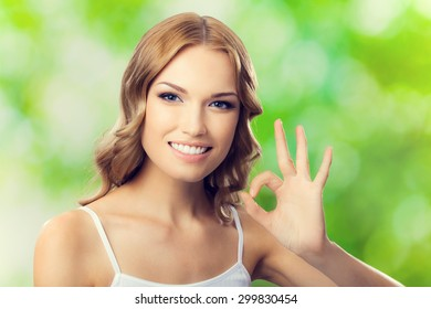 Portrait of beautiful young happy smiling lovely blond woman with okay gesture, outdoors