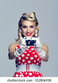 Portrait of beautiful young happy smiling woman, with no-name old film camera, taking picture, dressed in pin-up style. Caucasian blond model posing in retro fashion and vintage concept studio shoot.