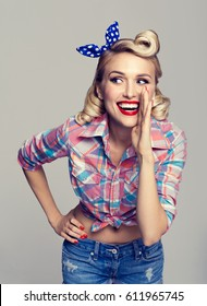 Portrait of beautiful young happy smiling woman, dressed in pin-up style. Caucasian blond model posing in retro fashion and vintage concept studio shoot, on grey background.