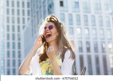 Portrait of beautiful young happy woman using her mobile phone in the city street with modern buildings