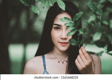 Portrait of beautiful young healthy asian woman with sportswear at green nature park background in morning, hipster style